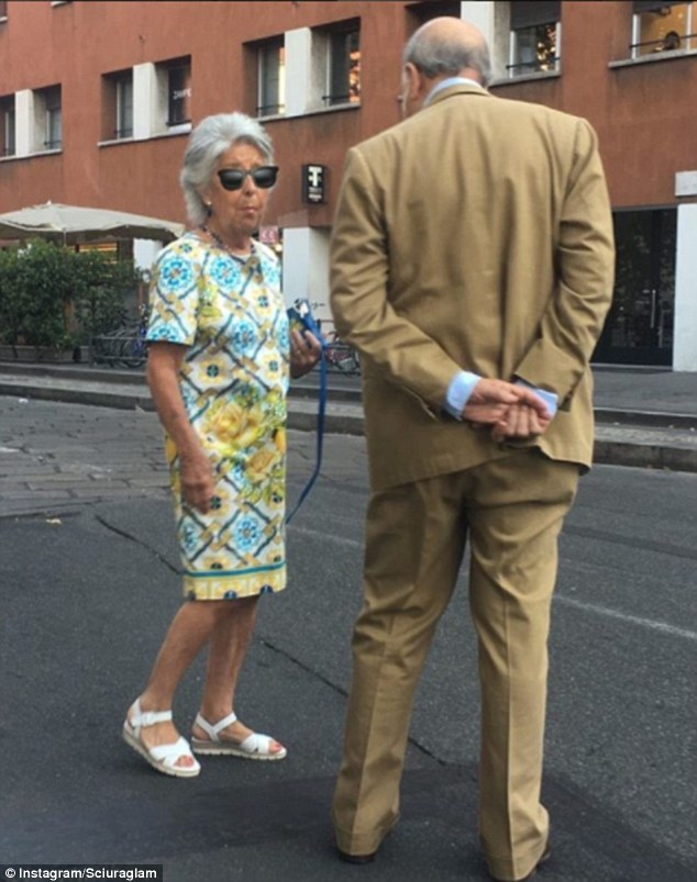 Angelo asks each woman permission to take their picture and the account is gaining popularity. Pictured: A woman in a bright patterned dress poses with a male companion in  a Milan street